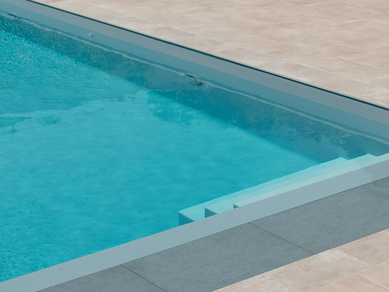 Réalisation Piscines & Concept - Piscine traditionnelle - membrane gris - margelles pierre naturelle - volet roulant immergé